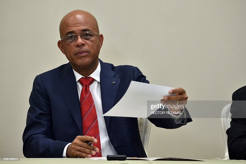 Haitian President Michel Martelly presents the signed agreement installing a transitional government on February 6, 2016 in Port-au-Prince, Haiti. Haitian politicians inked a last-minute agreement to install a transitional government, just hours before President Michel Martelly was scheduled to step down with no replacement in line. / AFP / HECTOR RETAMAL