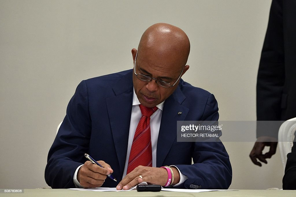 Haitian President Michel Martelly signs an agreement to install a transitional government on February 6, 2015 in Port-au-Prince. Haitian politicians inked a last-minute agreement to install a transitional government, just hours before President Michel Martelly was scheduled to step down with no replacement in line. / AFP / HECTOR RETAMAL