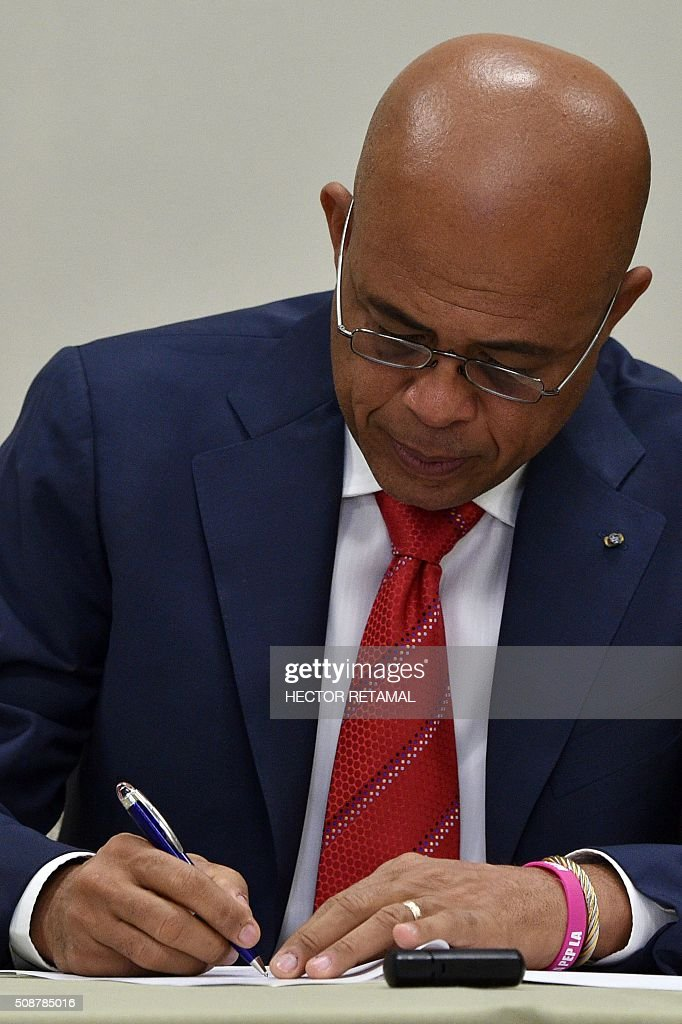 Haitian President Michel Martelly signs the agreement installing a transitional government on February 6, 2016 in Port-au-Prince, Haiti. Haitian politicians inked a last-minute agreement to install a transitional government, just hours before President Michel Martelly was scheduled to step down with no replacement in line. / AFP / HECTOR RETAMAL