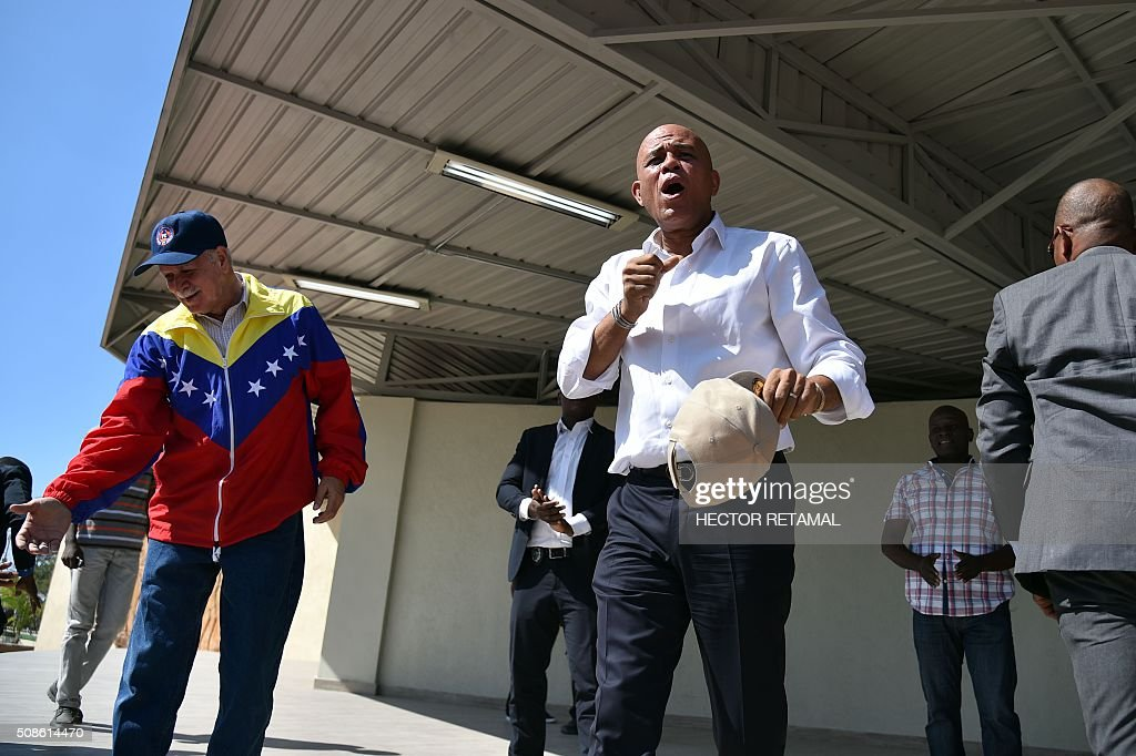 Haitian President, Michel Martelly sings as he visits Hugo Chavez Square, in Port-au-Prince, on February 5, 2016. Martelly's term ends on February 7, and with no successor in place, Haiti is facing a constitutional crisis. Haiti's electoral authority postponed the planned January 24 presidential run-off amid mounting opposition street protests and voting fraud allegations. / AFP / HECTOR RETAMAL