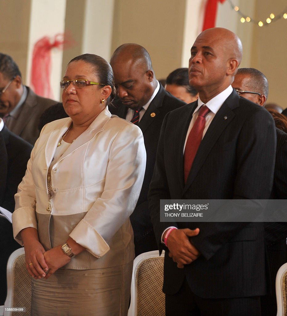 Haitian President Michel Martelly stands with his wife Sophia Martelly during ceremonies marking Haiti's 209th year of independance from France in 1804, in the northern city of Gonaives, 171 Km from Port-au-Prince, January 1, 2013. Martelly made a New Year plea for unity, urging his countrymen to rebuild together their shattered country almost three years after a devastating earthquake. Haiti, the poorest country in the Western hemisphere, has suffered a series of natural disasters throughout its history, with cyclones, hurricanes, torrential rains, floods and earthquakes battering the country. AFP PHOTO / Thony BELIZAIRE