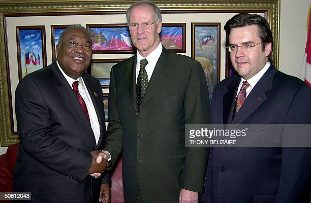 Haitian Prime Minister Gerard Latortue shakes hands with Canadian Foreign Minister Bill Graham while Denis Coderre President of the Queens Privy...