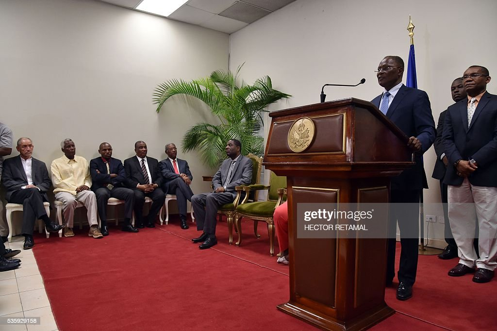 Haitian Provisional President Jocelerme Privert (R) speaks after receiving a special commission's investigative report on the 2015 Haitian election at the National Palace in Port-au-Prince, on May 30, 2016. The commission proposes rerunning the presidential election of 2015. / AFP / HECTOR