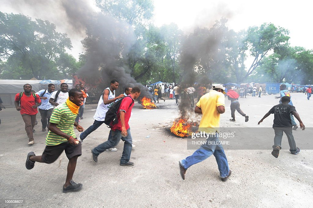 Haitian students run around burning tires as they demonstrate on May 25, 2010 near the presidential palace in Port-au-Prince against alleged violence by UN peacekeepers against Haitian students on May 24. The students demanded the UN leave Haiti. AFP PHOTO/Thony BELIZAIRE