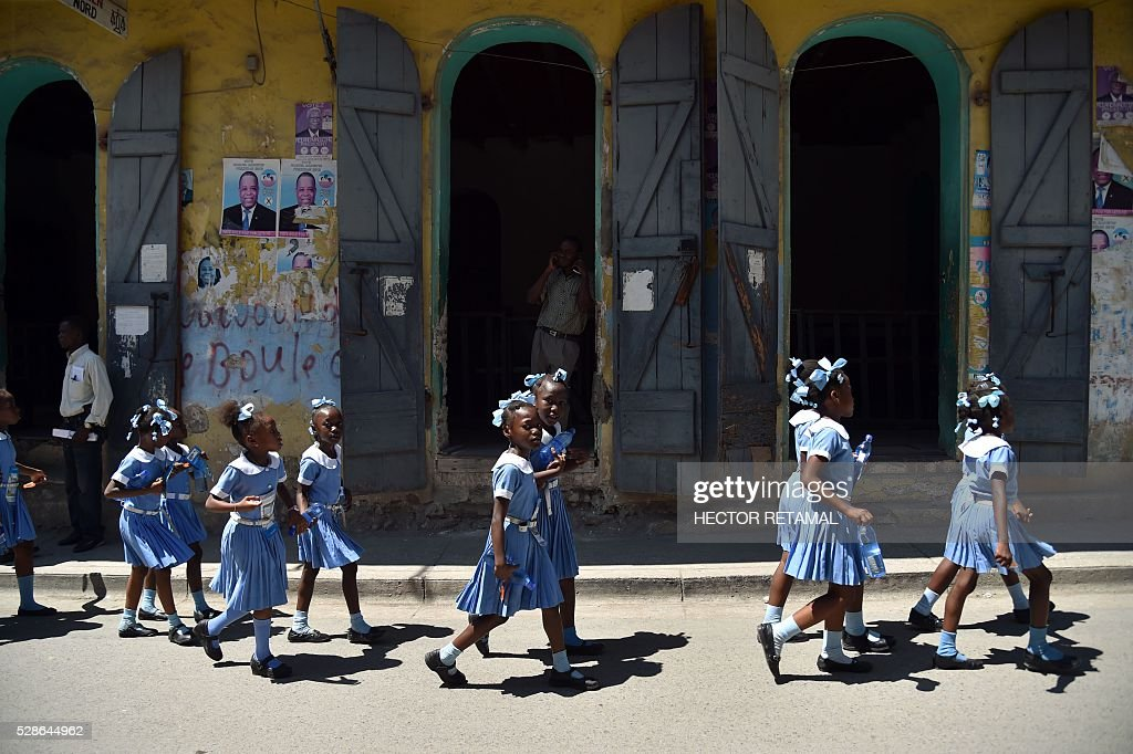 Haitian students walk to a security zone during an Earthquake and Tsunami Emergency drill in the city of Cap-Haitien, on May 6, 2016. The simulation exercise was organised by the Civil Protection Directorate, with the support of the UN Development Programme (UNDP). An estimated 4,500 people participated in the activities during the simulacre. / AFP / HECTOR
