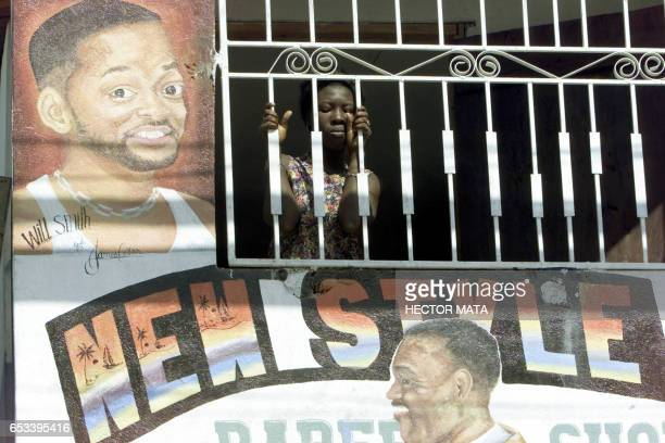 A Haitian woman peers through a window of a beauty salon in Port au Prince Haiti 27 November 2002 Several confrontations between pro and anti...
