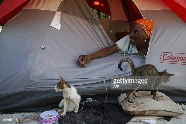A Haitian woman uses string to leash the cats she was able to rescue at a camp set up for people displaced from their homes on February 10 2010 in...