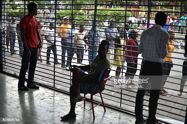TOPSHOT Haitians line up to vote at a polling station at the Lycee National of Petion Ville in the Haitian capital PortauPrince on November 20 2016...