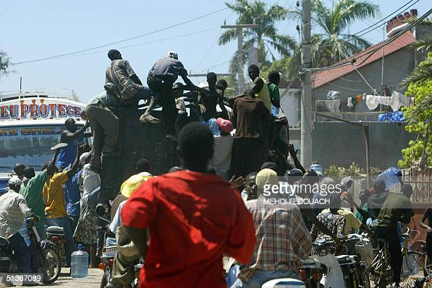 Haitians plunder a water truck 28 September 2004 in Gonaives where tension has mounted after floods killed more than 1100 people and residents...