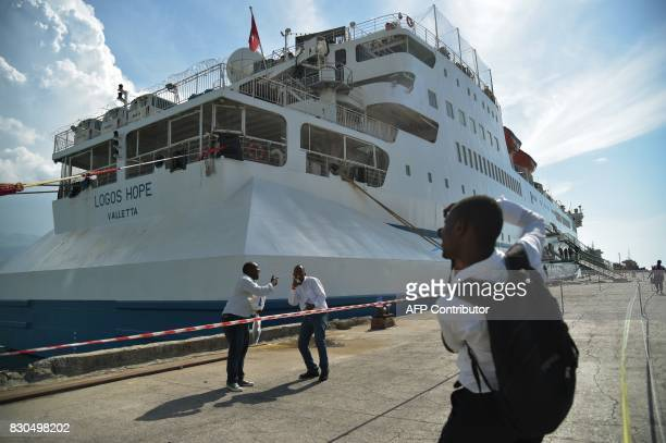 Haitians pose for a photograph after visiting the Logos Hope library ship in the Port of PortauPrince on August 11 2017 Logos Hope ship functions as...