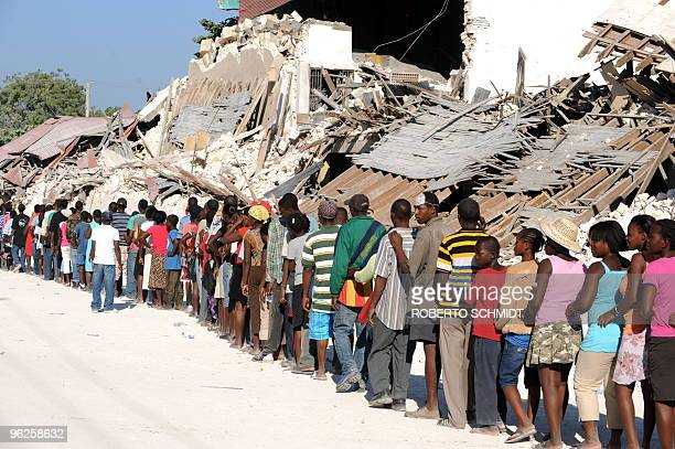 Haitians queue at a UN aid distribution point by the Presidential palace in PortauPrince on January 22 2010 More aftershocks rocked the Haitian...