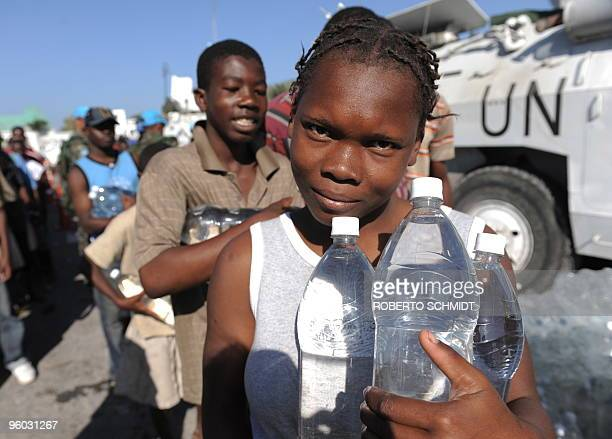 Haitians receive water at an aid distribution point outside the presidential palace in PortauPrince on January 22 2010 More aftershocks rocked the...