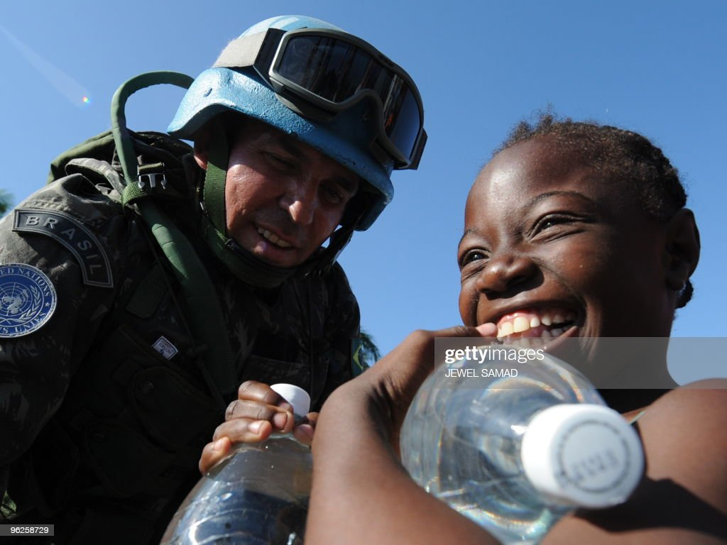 Haitians receive water from Brazilian UN peacekeepers at an aid distribution point by the Presidential palace in Port-au-Prince on January 22, 2010. More aftershocks rocked the Haitian capital today, as UN teams switched focus from search and rescue to relief efforts 10 days after a catastrophic earthquake demolished much of the city. AFP PHOTO / JEWEL SAMAD