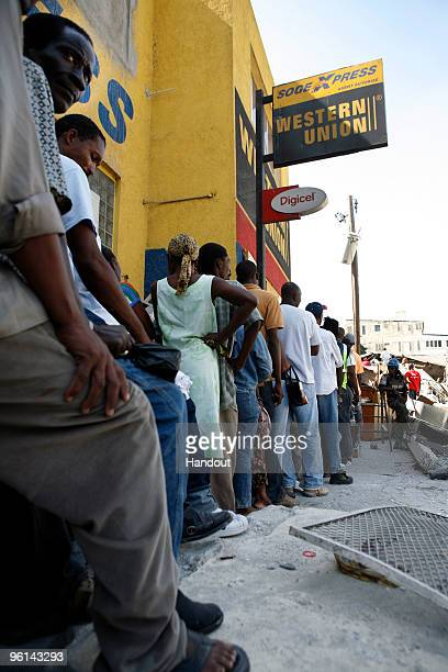 Haitians stand in line at a Western Union waiting for it to open January 23 2010 in PortauPrince Haiti Some banks attempted to reopen today after the...