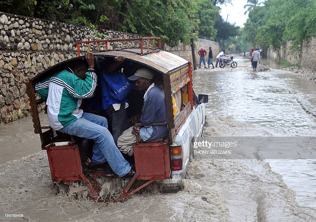 Haitians travel a flooded street in the aftermath of Hurricane Sandy October 25, 2012 in Port-au-Prince, Haiti. Hurricane Sandy barreled toward the Bahamas Thursday as a powerful category two storm, after battering Jamaica, Haiti and Cuba and claiming three lives so far. The US-based National Hurricane Center said the storm was packing winds of up to 105 miles (165 kilometers) per hour as it moved north, near the top of the category two range on the five-rung Saffir-Simpson wind scale. Forecasters predicted the storm would weaken somewhat over the next 48 hours. But Sandy will remain a hurricane as it passes over the Bahamas, according to the NHC's 1500 GMT advisory.