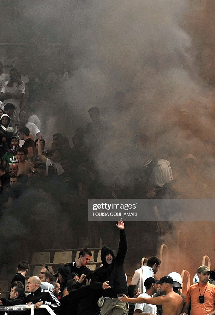 HNK Hajduk Split fans gesture through the smoke of burning flares and chairs during the UEFA Europa League football match against AEK Athens at the Olympic stadium in Athens on September 16, 2010.
