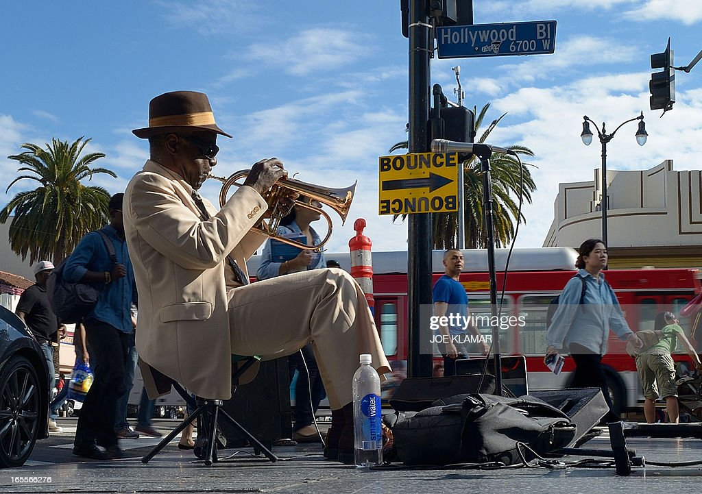 Haji Ahkba, founder and member of The Haji Ahkba Jazz Assembly, plays his trumpet at the intersection of Hollywood Boulevard and North Highland Street on April 04, 2013 in Hollywood, California. KLAMAR
