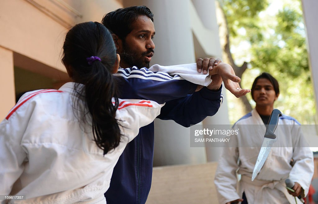 Hajibhai Rangrej (2L) displays basic Judo skills to unseen Indian female high school students as they participate in a camp for self defense in Ahmedabad on January 21, 2013. Increasing crime against women and girls with the recent Delhi gang-rape and many similar crimes in Gujarat state are compelling women and girls to protect themselves with basic defence skills like judo and karate. AFP PHOTO / Sam PANTHAKY