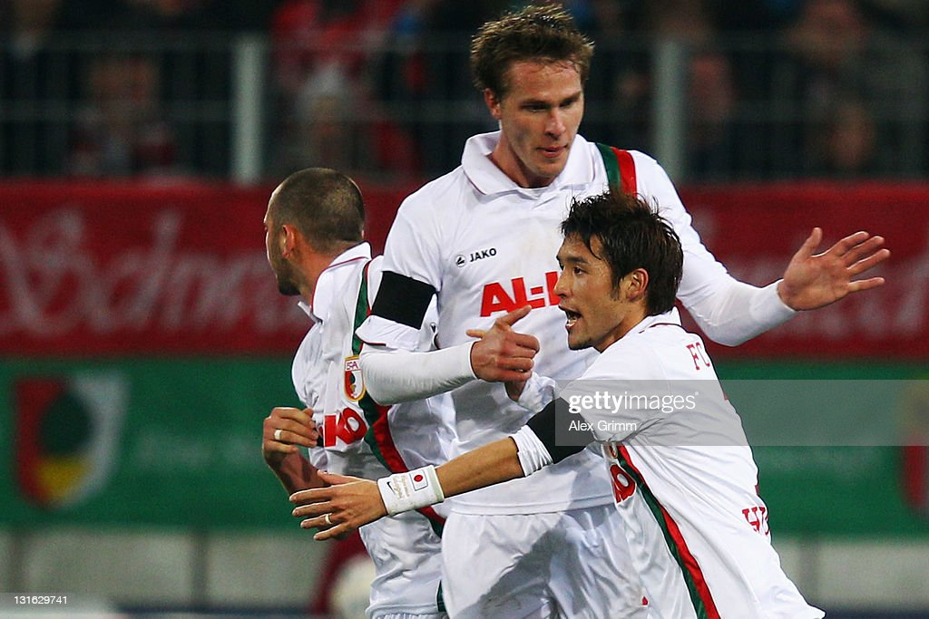 Hajime Hosogai of Augsburg celebrates his team's first goal with team mates during the Bundesliga match between FC Augsburg and FC Bayern Muenchen at...
