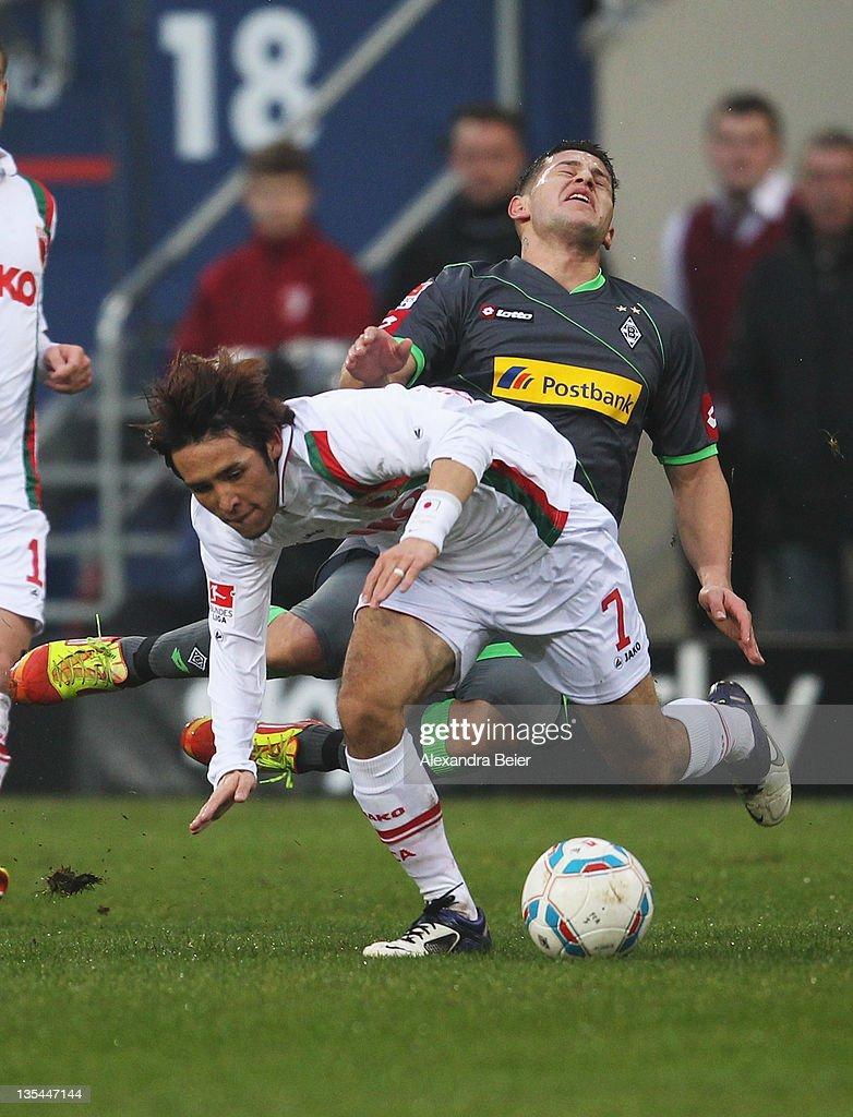 Hajime Hosogai of Augsburg fouls Raul Bobadilla of Moenchengladbach during the Bundesliga match between FC Augsburg and Borussia Moenchengladbach at...