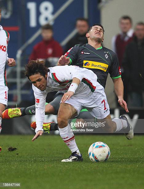 Hajime Hosogai of Augsburg fouls Raul Bobadilla of Moenchengladbach during the Bundesliga match between FC Augsburg and Borussia Moenchengladbach at...