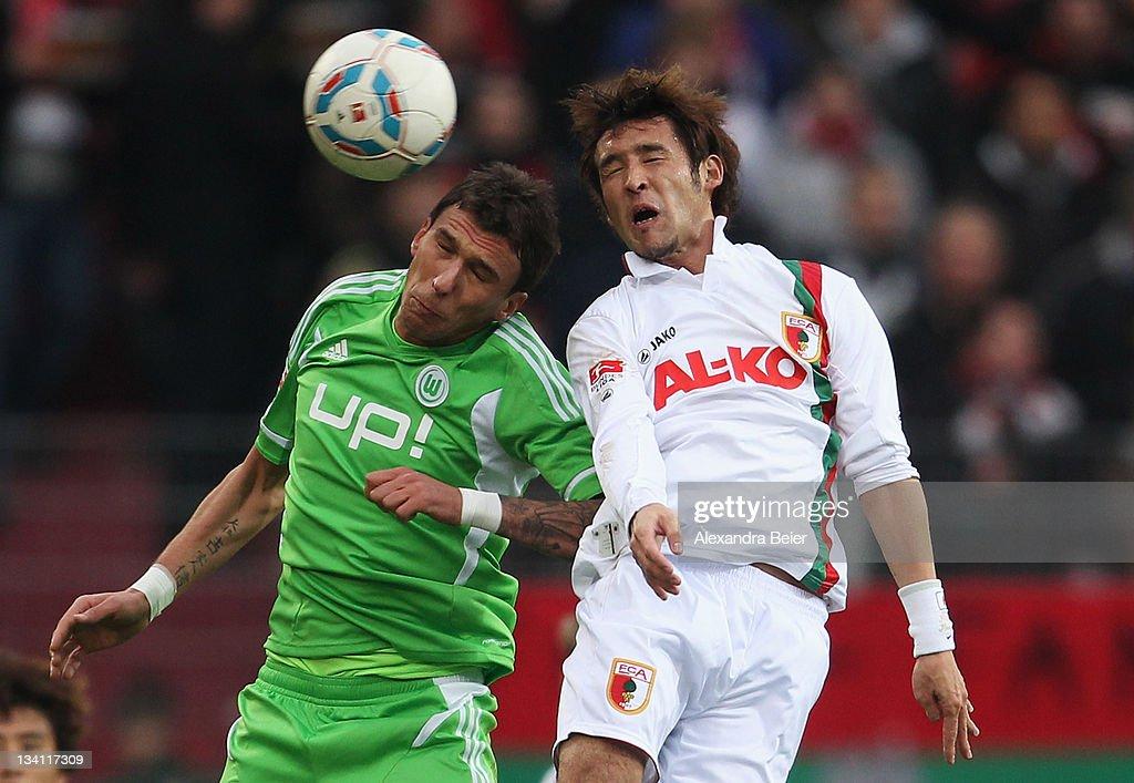 Hajime Hosogai of Augsburg heads for the ball with Mario Mandzukic of Wolfsburg during the Bundesliga match between FC Augsburg and VfL Wolfsburg at...