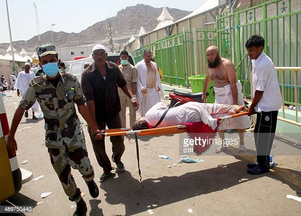 Hajj pilgrims and Saudi emergency personnel carry a woman on a stretcher at the site where at least 450 were killed and hundreds wounded in a...