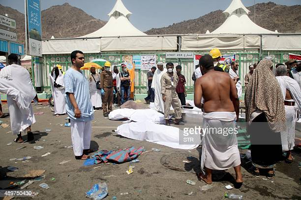 Hajj pilgrims and Saudi emergency personnel stand near bodies at the site where at least 450 were killed and hundreds wounded in a stampede in Mina...
