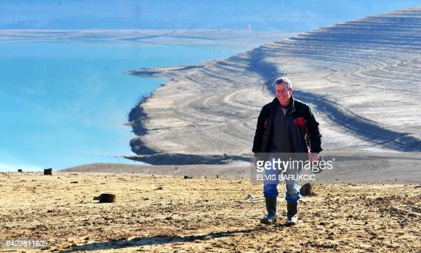 Hajrudin Kadric walks on the driedout lake bed of artificial Ramsko lake near the Bosnian town of Prozor some 120 km west of Sarajevo on February 16...