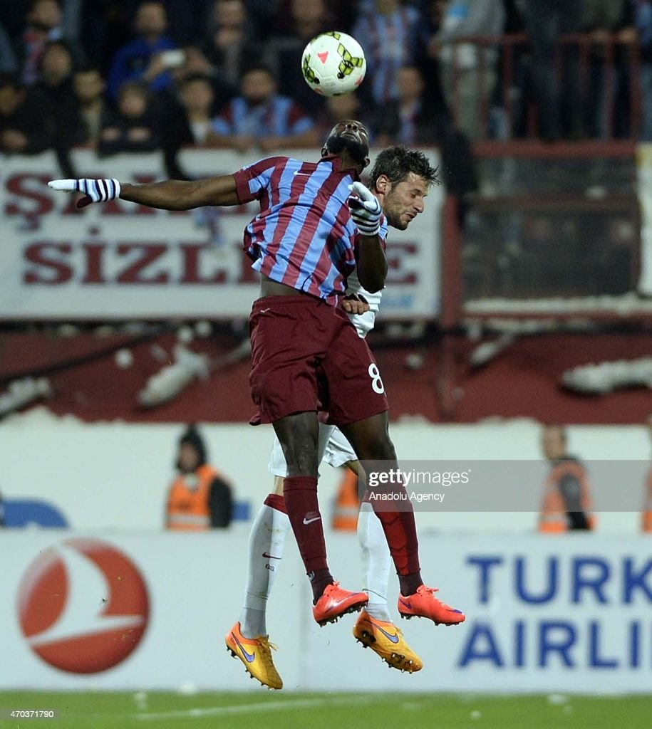 Hakan Balta (Rear) of Galatasaray in action against Yatabare (Front) of Trabzonspor during the Turkish Spor Toto Super League soccer match between Trabzonspor and Galatasaray at Avni Aker Stadium in Turkey on April 19, 2015.