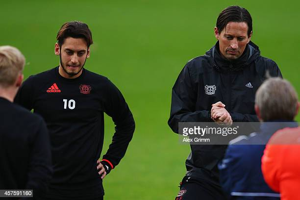 Hakan Calhanoglu listens as head coach Roger Schmidt talks during a Bayer Leverkusen training session ahead of their UEFA Champions League Group C...