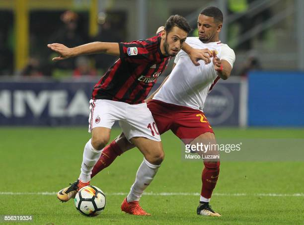Hakan Calhanoglu of AC Milan competes for the ball with Bruno Peres of AS Roma during the Serie A match between AC Milan and AS Roma at Stadio...