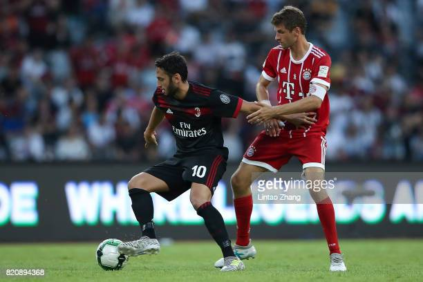 Hakan Calhanoglu of AC Milan competes for the ball with Thomas Mueller of FC Bayern during the 2017 International Champions Cup China match between...