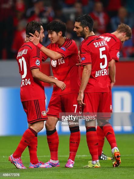 Hakan Calhanoglu of Bayer Leverkusen celebrates scoring their third goal with Son HeungMin and Emir Spahic of Bayer Leverkusen during the UEFA...
