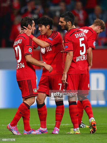 Hakan Calhanoglu of Bayer Leverkusen celebrates scoring their third goal with Son HeungMin and Emir Spahic of Bayer Leverkusen during the UEFA...