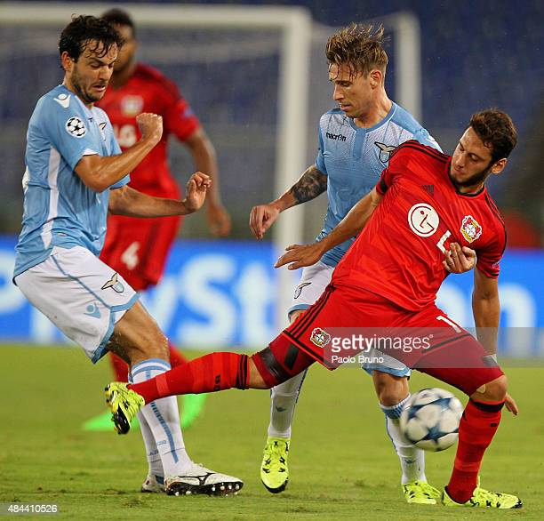 Hakan Calhanoglu of Bayer Leverkusen competes for the ball with Marco Parolo and Lucas Biglia of SS Lazio during the UEFA Champions League qualifying...