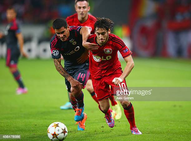 Hakan Calhanoglu of Bayer Leverkusen is challenged by Maximiliano Pereira of Benfica during the UEFA Champions League Group C match between Bayer 04...