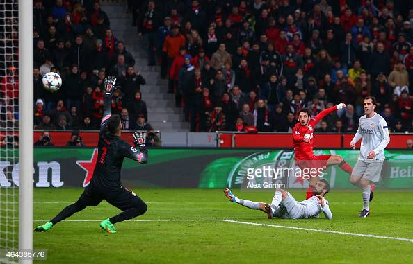 Hakan Calhanoglu of Bayer Leverkusen scores the opening goal past Miguel Angel Moya of Atletico Madrid during the UEFA Champions League round of 16...