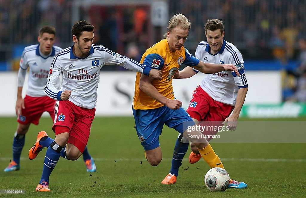 Hakan Calhanoglu of Hamburg, Havard Nielsen of Braunschweig and Marcell Jansen of Hamburg vie for the ball during the Bundesliga match between Eintracht Braunschweig and Hamburger SV at Eintracht Stadion on February 15, 2014 in Braunschweig, Germany.