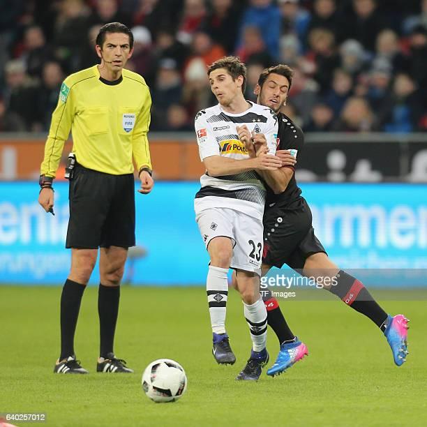 Hakan Calhanoglu of Leverkusen and Jonas Hofmann of Moenchengladbach battle for the ball during the Bundesliga match between Bayer 04 Leverkusen and...