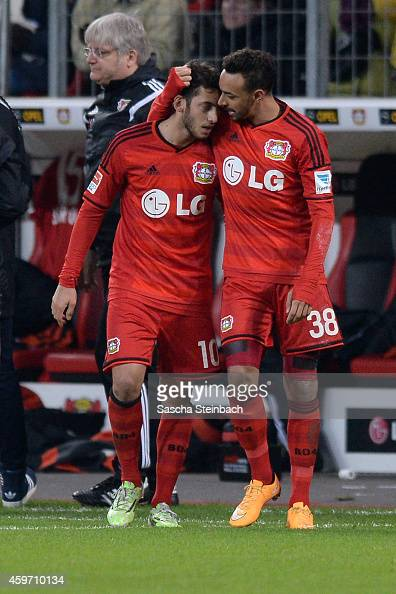 Hakan Calhanoglu of Leverkusen celebrates with team mate Karim Bellarabi after scoring his team's second goal and Lars Bender after scoring his...