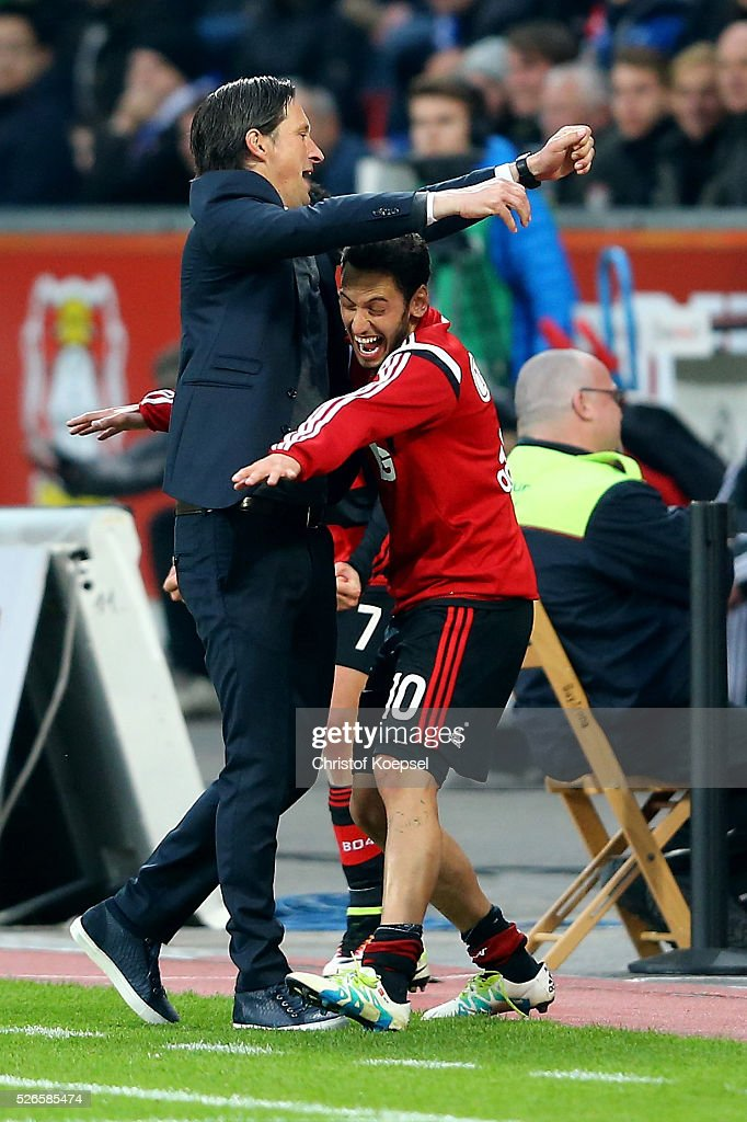 Hakan Calhanoglu of Leverkusen (R) embraces head coach <a gi-track='captionPersonalityLinkClicked' href=/galleries/search?phrase=Roger+Schmidt+-+Soccer+Manager&family=editorial&specificpeople=13515848 ng-click='$event.stopPropagation()'>Roger Schmidt</a> of Leverkusen (L) after the Bundesliga match between Bayer Leverkusen and Hertha BSC Berlin at BayArena on April 30, 2016 in Leverkusen, Germany. The match between Leverkusen and Belrin ended 2-1.