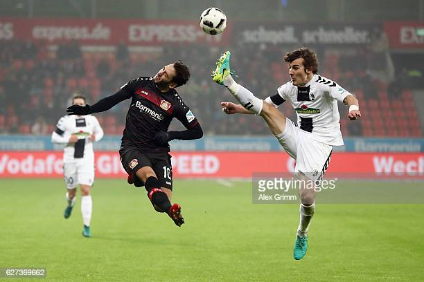 Hakan Calhanoglu of Leverkusen is challenged by Caglar Souyuencue of Freiburg during the Bundesliga match between Bayer 04 Leverkusen and SC Freiburg...