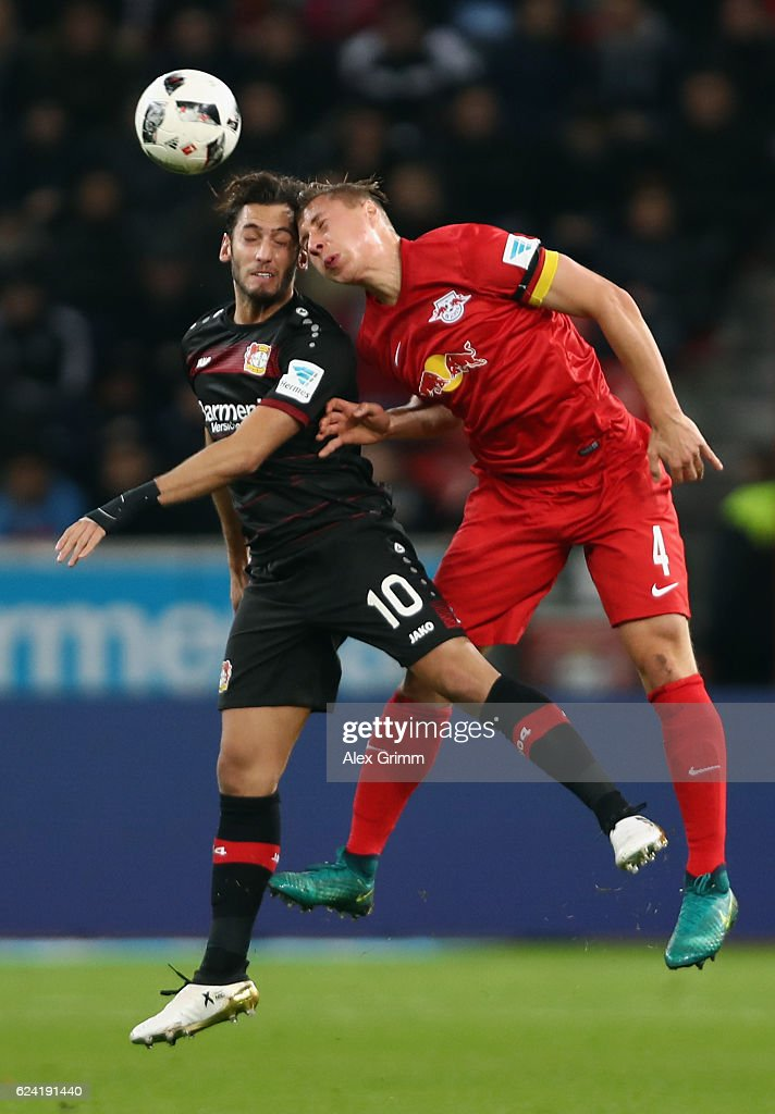 Hakan Calhanoglu (L) of Leverkusen jumps for a header with Willi Orban of Leipzig during the Bundesliga match between Bayer 04 Leverkusen and RB Leipzig at BayArena on November 18, 2016 in Leverkusen, Germany.