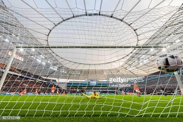Hakan Calhanoglu of Leverkusen shoot the first goal against Goalkeeper Michael Esser of Darmstadt during the Bundesliga match between Bayer 04...