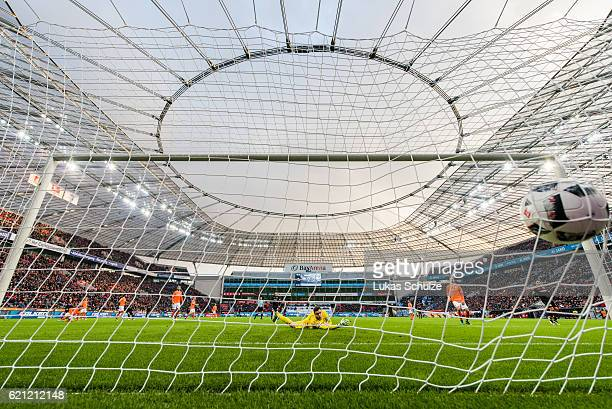 Hakan Calhanoglu of Leverkusen shoot the first goal against Goalkeeper Michael Esser of Darmstadt during the Bundesliga match between Bayer 04...