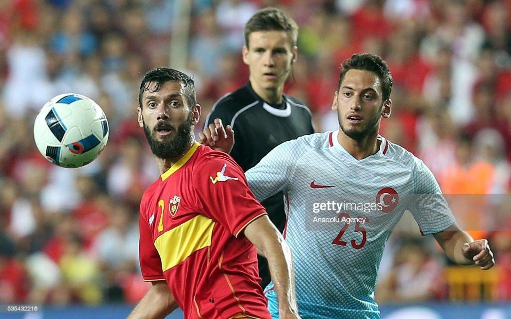Hakan Calhanoglu (R) of Turkey and Scekic (L) of Montenegro vie for the ball during the friendly football match between Turkey and Montenegro at Antalya Ataturk Stadium in Antalya, Turkey on May 29, 2016.