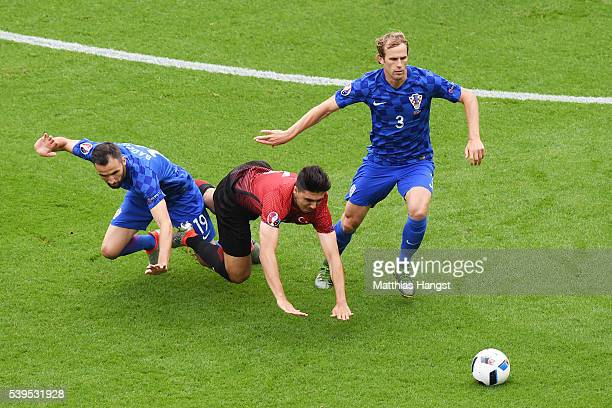 Hakan Calhanoglu of Turkey competes for the ball against Milan Badelj and Ivan Strinic of Croatia during the UEFA EURO 2016 Group D match between...