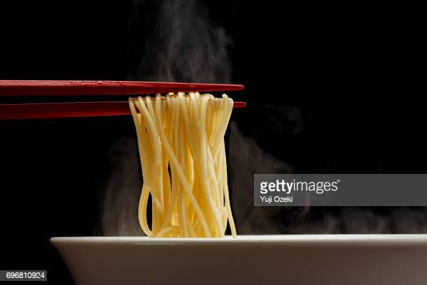 Hakata Ramen noodle lifted up by red chopsticks with steams against black background