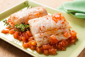 two hake fillets with onion, tomato and red pepper on a green square plate on a wooden background and green napkin..